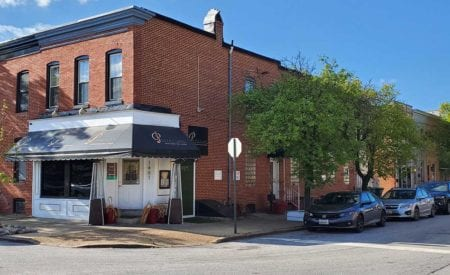 Brick exterior of corner restaurant property with white entrance and awning